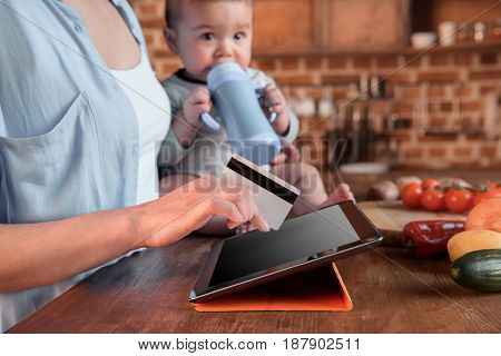 Cropped Shot Of Woman And Baby Boy Shopping Online With Digital Tablet And Credit Card