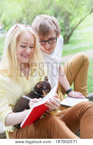 Young Attractive Couple Wearing Glasses Is Working Or Studying With Laptop Book Note And Pen Sitting