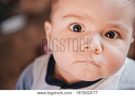 Portrait of funny little boy looking at camera with serious expression