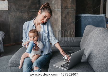 Young Mother With Baby Boy Remote Working And Using Laptop During Conversation On Smartphone