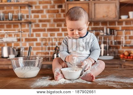 Adorable little boy playing with flour and sitting on kitchen table. Domestic life concept