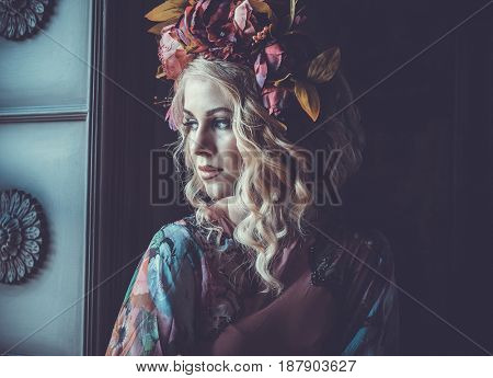 Beautiful woman in a dress of floral colors stands in the palace