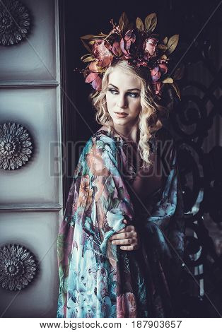 Beautiful woman in a dress of floral colors with wreath of flowe
