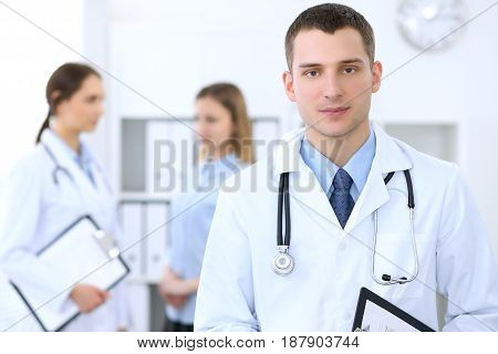 Friendly male doctor  on the background with patient  and physician in hospital. High level and quality medical service concept.