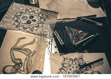Top view of different unusual tattoo pictures and marker pens situating on table. Paint concept. Close up