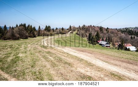 mountain meadow with hiking trail few houses forest and clear sky bellow Jakubovsky vrch in Javorniky mountains in Kysuce region of Slovakia during nice spring day