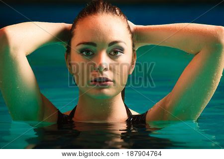 Portrait of sexy seductive woman in swimming pool water. Young attractive alluring girl. Top view.