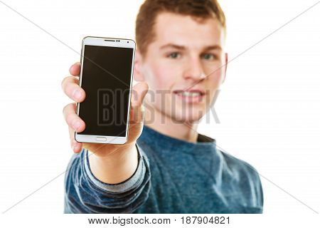 Communication and advertisement. Happy young man showing cell phone smartphone black blank screen isolated on white