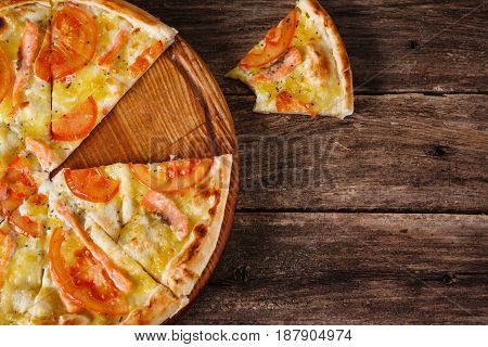 Fresh italian pizza with cut in slices served on rustic wooden table, flat lay. Calories, junk food, bad habits. Dark wooden background with free space for text.
