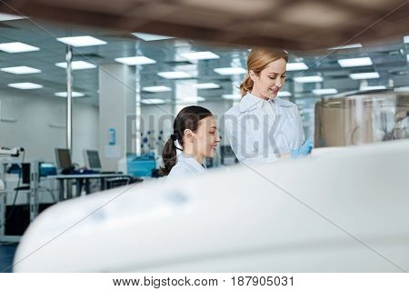 I watching you. Attractive blonde female keeping smile on face wearing white smock while standing near her assistant