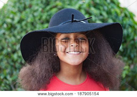 Pretty girl with long afro hair in the garden with a elegant black hat