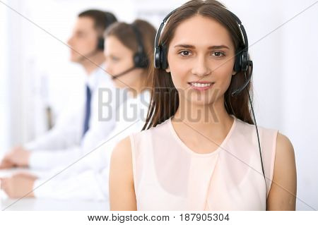 Call center operators. Focus at young beautiful business woman in headset.