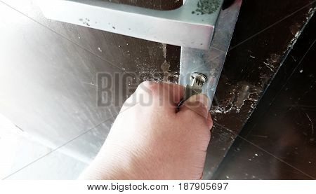 Close-up of hand with key unlocking the metallic door.