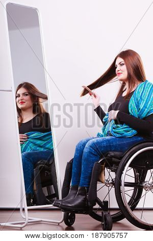Disability beauty invalid happiness concept. Disabled girl looking at mirror. Crippled lady sitting at wheelchair doing combing her hair.
