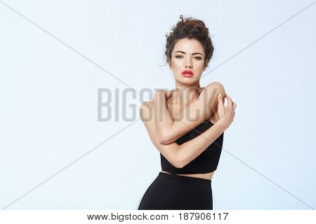 Young attractive girl with bright make up in black retro underwear posing over blue background. Copy space.
