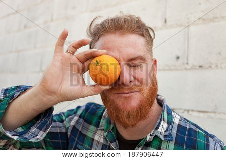 Red haired man with a orange before his eye
