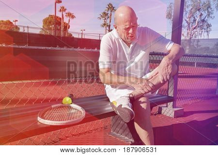Senior male tennis player with leg pain sitting on bench at court