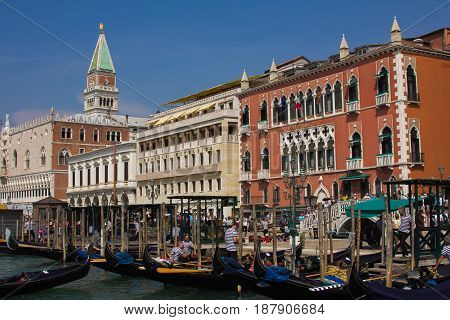 VENICE, ITALY - MAY 23, 2017: View of the historical Doge's Palace with venetian gondolas floating on the canal grande on sunny clear blue sky, Venice, Italy