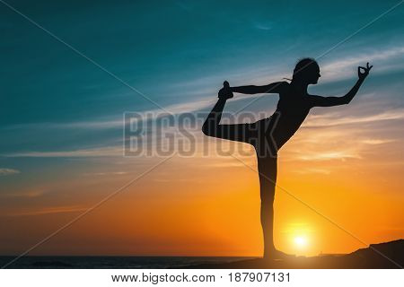 Silhouette young woman, exercise on the beach at amazing sunset. Yoga and Health lifestyle.
