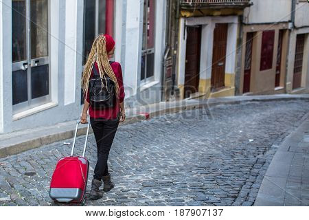 Traveler girl walking in old european town with red suitcase.