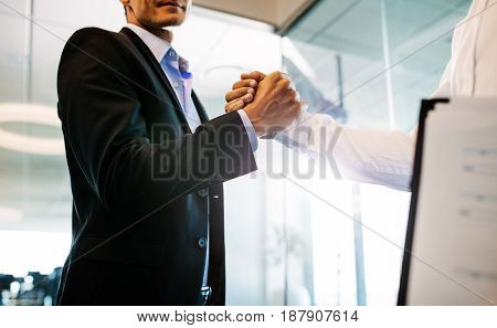 Two businessman shaking hands in office. Close up of handshake after a successful deal.