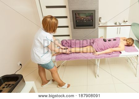 Spa relaxation healthy pleasure concept. Woman lying on stomach female masseuse doing legs and feet massage with hot stones