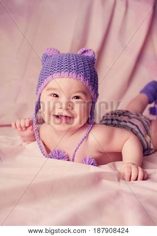 Expressive adorable happy baby smiling while lying in bed