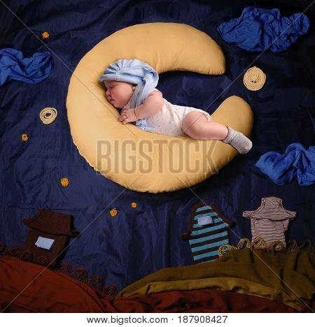 Studio portrait of infant baby girl wearing a stocking cap and pajamas, sleeping on a moon shaped pillow against textile decoration of a night village