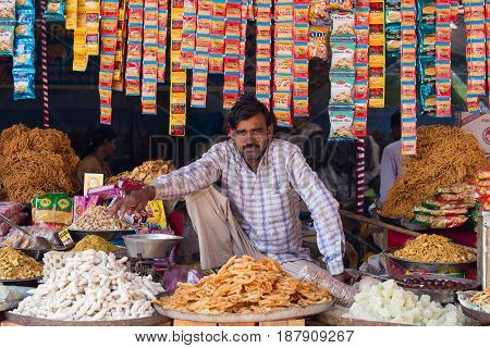 PUSHKAR INDIA - OCTOBER 28 2014: Unidentified Indian man sells sweets in the trade shop during the annual Pushkar Camel Mela. This fair is the largest camel trading fair in the world