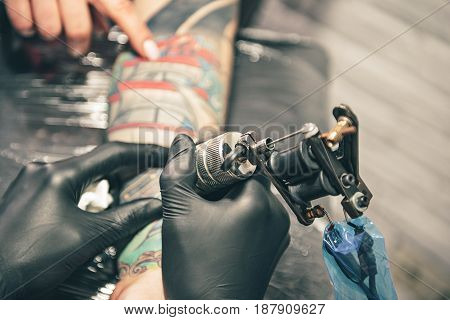 Focus on close up tattoo machine which keeping male in hand. He creating picture on female hand