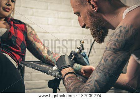 Low angle serene bearded man creating tattoo on woman hand. She leaning on chair