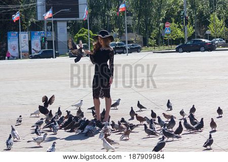 Donetsk Ukraine - May 17 2017: Girl in a hat feeding pigeons in the central square of the city