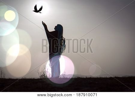 Silhouette Muslim Arabic woman praying with her hands up