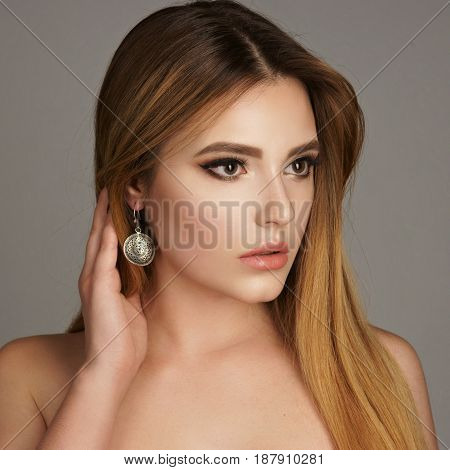 Beautiful model with long brown straight hair and jewelry. Perfect makeup. Girl wearing earrings.