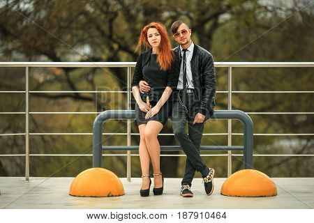 Couple In Love. Modern Haircuts. Handsome Guy In Headphones And Pretty Girl With E-cigarette Posing
