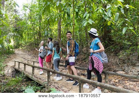 People Group With Backpacks Walking On Bridge Trekking On Forest Path, Young Men And Woman On Hike Mix Race Tourists Hiking