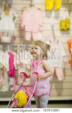 Happy little girl playing with her toy, pushing doll, smiling