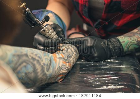 close up female drawing tattoo on arm of male with special equipment in salon