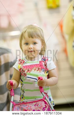 Happy little girl playing with a stroller in a bright dress looking at the camera