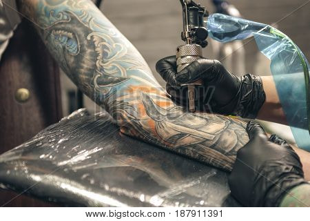 Female master creating tattoo on hand of man with special device in salon. Close up