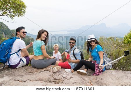 People Group With Backpacks Sitting On Mountain Top Taking Selfie Photo, Young Men And Woman Tourists Backpackers On Hike