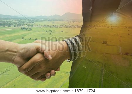 Double exposure of handshake with agriculture background with the fake flare the partnership between business man and farmer concept