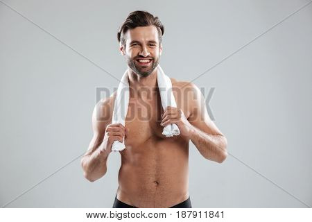 Smiling half-naked man posing with towel at camera isolated