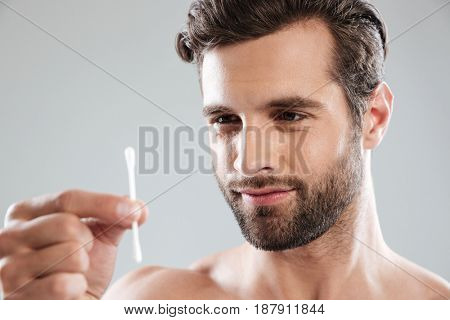 Focused smiling young man looking at ear stick in his hands isolated over grey