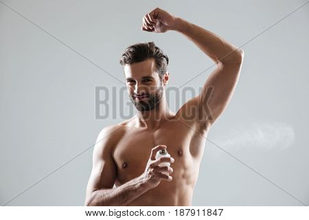 Young smiling half-naked man looking camera while using perfume isolated