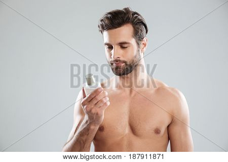 Young thoughtful bearded man focused at perfume isolated