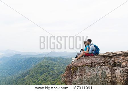 Couple With Backpacks Sit Embracing On Mountain Top Enjoy Landscape, Young Man And Woman Tourist Backpackers On Hike