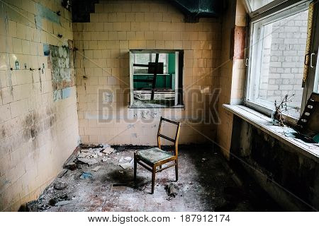 Room inside an old abandoned building, chair in the middle of the ruined room