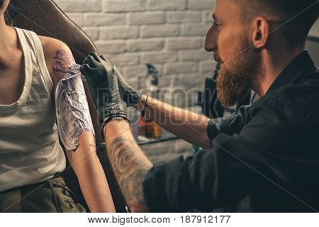 Side view bearded male creating temporary tattoo on arm of client