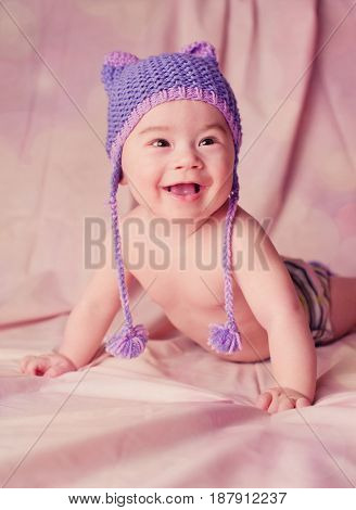 Portrait of a beautiful 6 months baby smiling dressed in funny knitted hat with kitty ears